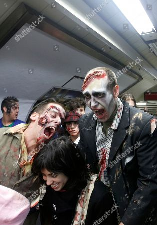 People dressed and made up as Zombies try to scare a passenger on the platform of a metro train station during the annual Zombie march in Madrid, . The zombie march is in homage by fans to the Zombie film genre and to U.S. director George A. Romero, famous for his Zombie horror movies