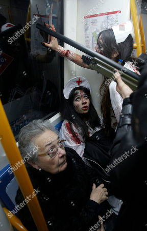 A passenger looks at people dressed and made up as Zombies on a metro train during the annual Zombie march in Madrid, . The zombie march is in homage by fans to the Zombie film genre and to U.S. director George A. Romero, famous for his Zombie horror movies