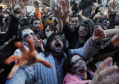 People dressed and made up as Zombies react, during the annual Zombie march, in Madrid, . The zombie march is a homage to the Zombie film genre and to U.S. director George A. Romero, famous for his Zombie horror movies