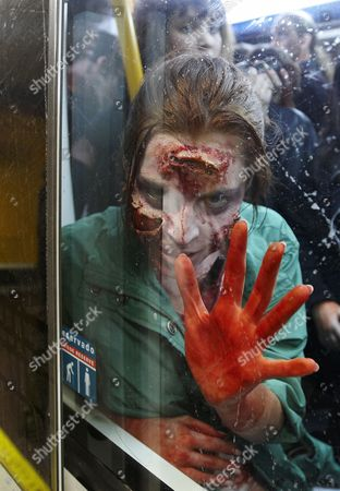 A woman dressed and made up as a Zombie reacts from inside a metro train during the annual Zombie march in Madrid, . The zombie march is in homage by fans to the Zombie film genre and to U.S. director George A. Romero, famous for his Zombie horror movies