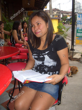 Prostitute 'Yo', 31 sitting at the Lucky Bar in Pattaya, clutching the dictionary she uses to communicate with clients. Johnny Briggs paid her GBP15 to spend the night with her at the nearby Dynasty Hotel.