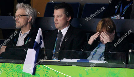 Finland President Tarja Halonen, right, touches her brow while watching Finland's women's hockey team play Sweden in the women's bronze medal ice hockey game at the Vancouver 2010 Olympics in Vancouver, British Columbia, . and Doctor Pentti Arajarvi is at left. Man at center is unidentified. Finland won 3-2