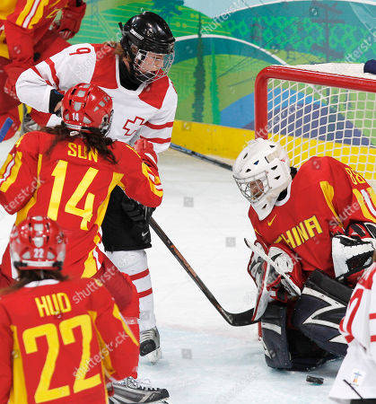 Switzerland's forward Stefanie Marty (9) scores past China's goalie Jia Dandan in the second period in a women's classifications hockey game at the Vancouver 2010 Olympics in Vancouver, British Columbia, . China's forward Huo Cui and forward Sun Rui are at lower left