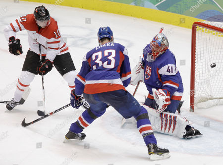 Canada's Brenden Morrow (10) watches a shot by teammate Ryan Getzlaf, not visible, go into the net for a goal against Slovakia's goalie Jaroslav Halak in the second period of a men's semifinal round ice hockey game at the Vancouver 2010 Olympics in Vancouver, British Columbia, . Also defending is Zdeno Chara (33