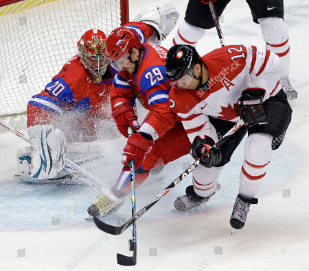 Canada's Jarome Iginla (12) tries to shoot past Russia's Sergei Fedorov (29) and goalie Evgeni Nabokov (20) in the first period of a men's quarterfinal round ice hockey game at the Vancouver 2010 Olympics in Vancouver, British Columbia