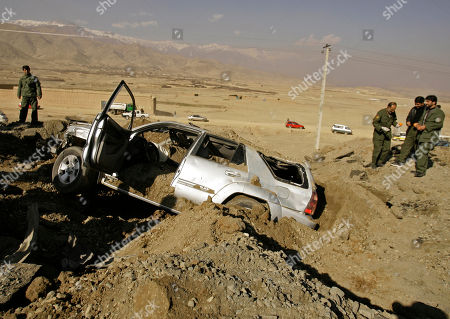 Afghan security forces stand next to a vehicle destroyed in a roadside bomb on the outskirts of Kabul, Afghanistan, . The vehicle was a part of a convoy carrying a provincial council member from Wardak province, Mohammad Rafi Tahiry, killing a bodyguard and wounding five others. Interior Ministry said