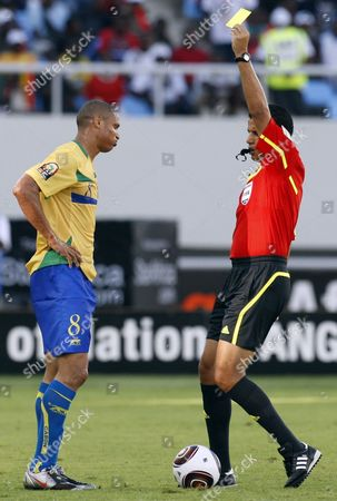 Mohamed Benouza Gabon's captain Daniel Cousin, left, is shown a yellow card by referee Mohamed Benouza from Algeria, right, for tackling Zambia's captain Christopher Katongo, unseen, during their African Cup of Nations Group D soccer match at the Ombaka National Stadium in Benguela, Angola, . Zambia beat Gabon 2-1