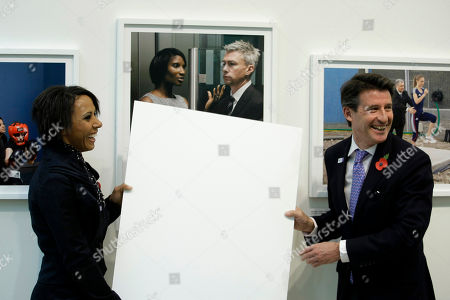 British Olympians Dame Kelly Holmes, left, and Lord Sebastian Coe, right, react as they pretend to reveal a portrait by photographer Brian Griffin as his photographic exhibition is unveiled during a launch to mark 1000 days to go until the start of the London 2012 Olympics at the National Portrait Gallery in London, . The Road to 2012 Project will take the form of 100 photographic portraits by various photographers of the people around Britain involved in making the 2012 Olympic games happen