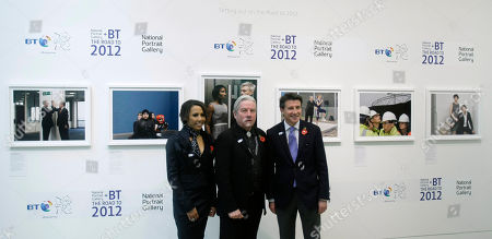 British Olympians Dame Kelly Holmes, left, and Lord Sebastian Coe, right, pose with photographer Brian Griffin, center, as his photographic exhibition is unveiled during a launch to mark 1000 days to go until the start of the London 2012 Olympics at the National Portrait Gallery in London, . The Road to 2012 Project will take the form of 100 photographic portraits by various photographers of the people around Britain involved in making the 2012 Olympic games happen
