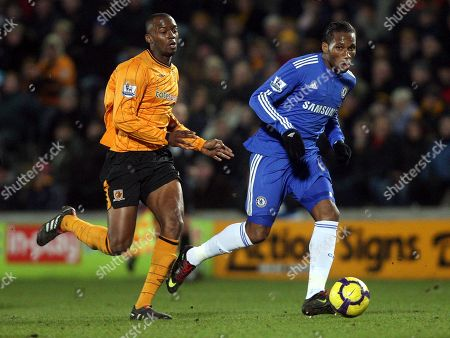 Chelsea's Didier Drogba, right, has a shot towards goal past Hull City's Stephen Mouyokolo, left, during their English Premier League soccer match at the KC Stadium, Hull, England, . (AP Photo/Scott Heppell) ** NO INTERNET/MOBILE USAGE WITHOUT FOOTBALL ASSOCIATION PREMIER LEAGUE(FAPL)LICENCE. CALL +44