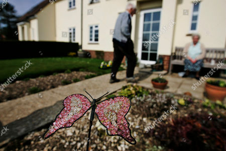A butterfly made of crystals and wire decorates the garden of Betty Smith, 79, and her husband Alan's house, background, at the village of Linkenholt in southern England, . The Smiths hold the key to the church which is ussually closed, but has a mass every month. The whole estate is up for sale _ as a whole _ with the only part of Linkenholt not on the block is the local church. All the village's 21 cottages, grand manor house, lush green cricket pitch and accompanying pavilion, are part of an estate that also encompasses 1,500 acres of farmland and another 425 of woods. The 40 or so residents, many of whom have lived here all their lives, hope any new owner who will have to pay at least 23 million british pounds (some 32 million US dollars), will keep the estate together and resist the urge to parcel off the land located just 75 miles (120 kilometers) southwest of London