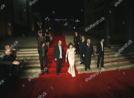 """Stock Image of Roman Duris, Cedric Klapisch, Juliette Binoche From left to right, French actor Roman Duris, French Director Cedric Klapisch and French actress Juliette Binoche walk the red carpet during the ahead of the screening of the movie """"Paris"""" at the opening of the French Film Festival in Beijing, China"""