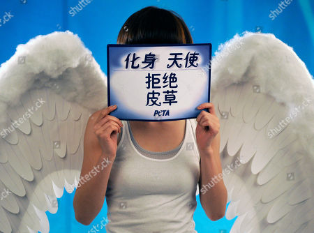 "Sun Li Chinese actress Sun Li dressed as an angel blocks her face with a sign that reads: ""Be an angel, Don't wear fur"" during a photo shoot for a new anti-fur ad for People for the Ethical Treatment of Animals (PETA) Asia in Beijing"