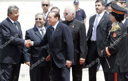 Moammar Gadhafi, Silvio Berlusconi Italian Premier Silvio Berlusconi, shakes hands with Tunisian industrialist Tarak Ben Ammar as Libyan leader Moammar Gadhafi, right, with black uniform, looks, after landing at Rome's Ciampino airport, . Gadhafi is on a three-day official visit to Italy