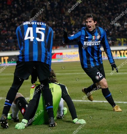 Mario Balotelli, Diego Milito, Sebastien Frey Inter Milan Argentine forward Diego Milito, at right in background, celebrates with his teammate Inter Milan forward Mario Balotelli after scoring during an Italian Cup semifinal first leg soccer match between Inter Milan and Fiorentina, at the San Siro stadium in Milan, Italy, . Fiorentina goalkeeper Sebastien Frey, of France, is seen on the ground between them
