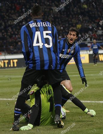 Mario Balotelli, Diego Milito, Sebastien Frey Inter Milan's Argentine forward Diego Milito, at right in background, celebrates with his teammate Inter Milan forward Mario Balotelli, n. 45, after scoring during an Italian Cup semifinal first leg soccer match between Inter Milan and Fiorentina, at the San Siro stadium in Milan, Italy, Wednesday, Feb.3, 2010. Fiorentina goalkeeper Sebastien Frey, of France, is seen on the ground between them