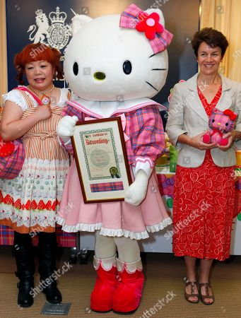"""Hello Kitty, Yuko Yamaguchi, Rachel Bayfield Hello Kitty in its original tartan blouse and ribbon, accompanied by Hello Kitty designer Yuko Yamaguchi, left, of Sanrio Co., and British Embassy First Secretary Rachel Bayfield, right, holds the Hello Kitty Tartan certificate by the International Tartan Index during a news conference to unveil """"Official Hello Kitty Tartan"""" products at British Embassy in Tokyo, Japan, . The special tartan items will be sold as part of memorabilia to mark the 35th anniversary of the birth of the Japan's most popular feline character Kitty White who is set to live in suburban London"""