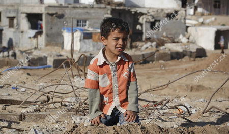 A Palestinian boy sits on rubble in an area that was destroyed during Israel's January 2009 Gaza offensive, during a visit from 60 European parliamentarians traveling with British Labour Party lawmaker Gerald Kaufman, not pictured, in the Jebaliya refugee camp, northern Gaza Strip, . Israelis who authorized the use of white phosphorous in densely populated Gaza should be tried for war crimes, Kaufman said Friday, after entering the Hamas-ruled territory with 60 European parliamentarians. Human rights groups have alleged that both Israel and Hamas committed war crimes during Israel's three-week offensive against Gaza, which ended a year ago
