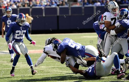 New York Giants linebacker Clint Sintim (97) tackles Oakland Raiders Jonathan Holland (23) during of an NFL football game, in East Rutherford, N.J