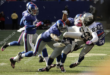 Jonathan Holland Oakland Raiders' Jonathan Holland (23) is tackled by New York Giants linebacker Jonathan Goff (54) and teammate Clint Sintim (97) during the second half of an NFL football game, in East Rutherford, N.J