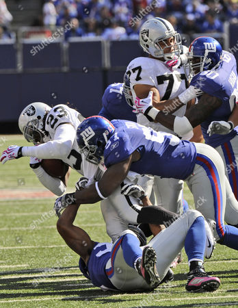 Oakland Raiders wide receiver Jonathan Holland (23) is tackled by New York Giants linebacker Clint Sintim (97) in the first quarter of an NFL football game, in East Rutherford, N.J