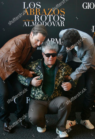"""Pedro Almodovar, Ruben Ochandiano, Asier Etxeandia Actors Ruben Ochandiano, left, and Asier Etxeandia, right, help Director Pedro Almodovar, center, stand up after a photocall for their new movie """"Los Abrazos Rotos"""" (Broken Embraces) in Madrid, on"""