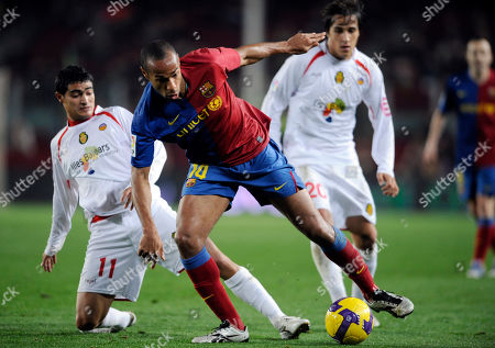 Stock Image of Thierry Henry, Oscar Guido, Gonzalo Castro FC Barcelona's Thierry Henry, from France, center, duels for the ball with Mallorca's Gonzalo Castro, left, and Gonzalo Castro during their semifinal Copa del Rey soccer match at Camp Nou Stadium in Barcelona, Spain