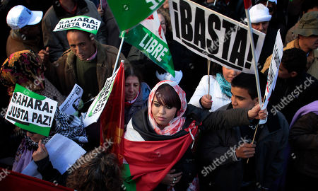"""People holds banners reading, """"Enough"""", top right, and """"Sahara Just Peace"""", during a march in support of Aminatou Haidar, a western Sahara independence activist who has been on a hunger strike for over a month in Madrid, . The activist from the disputed territory of Western Sahara has reportedly been flown back home"""