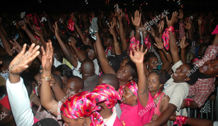 Stock Photo of Ugandan fans cheer American R&B superstar R Kelly best known by the stage name R. Kelly performing in Uganda's capital city Kampala organized by Zain Uganda,. The American R&B and soul singer song writer, occasional rapper, and record producer performed before a crowd of about 30,000 fans