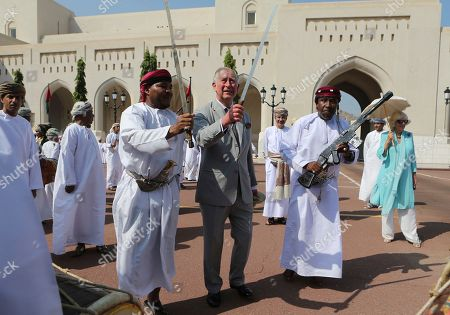 Stock Image of Britain's Prince Charles center, dances with a sword with a group of Omani traditional dancers in Muscat, Oman, . Prince Charles and his wife Camilla, right, have started a three-nation royal tour of the Gulf in Oman. Prince Charles landed in Muscat on Friday night, greeted at the airport by Omani Heritage and Culture Minister Sayyid Haitham Bin Tariq Al Said
