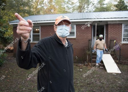 Bill Jones, 77, points towards a pile of debris removed from his home that was heavily damaged by floodwaters caused by rain from Hurricane Matthew in Nichols, S.C., . Nearly a month since floodwaters consumed the town, few have returned. The fear is that many never will. A stew of contaminants stood inches to feet deep in homes for a week. As it receded, toxic black mold grew rampant, leaving nearly all of the town's 261 homes uninhabitable. Few, if any, had flood insurance