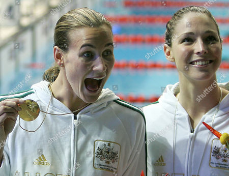 Australia's Giaan Rooney, silver, right, and Australia's Sophie Edington, gold, pose for photographers after the medal ceremony for the Women's 100m backstroke at the Commomwealth Games at the Sports and Aquatic Center in Melbourne, Australia