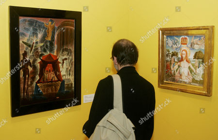 A visitor looks at paintings of Austrian artist Ernst Fuchs at the Jewish Museum in Vienna, Ausatria. Fuchs died at a hospital in Vienna, at the age of 85