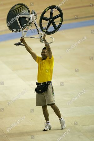 Absalon Martinez The coach of the Colombia's cycling team, Absalon Martinez holds up the bicycle of Diana Garcia after she defeated Cuba's Lizandra Guerra for the women's sprint cycling final at the Pan American Games in Rio de Janeiro