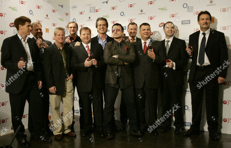 """Bono Irish singer and activist Bono of U2, center, accompanied by UK managers of mobile industry operators and retailers, presents new mobile handsets during a photo call in central London, . Bono presented the latest brands including mobile operators and retailers from across the UK to join Product (RED) range, an economic initiative where companies are licenced to sell """"Red"""" branded products to raise funds for the Global Fund-financed programmes to help fight AIDS in Africa. From left to right, Matthew Key, CEO of O2 UK, Tom Alexander, CEO of Virgin Mobile, Jim Hyde, Managing Director of T-Mobile, Andy Dewhurst CEO of Tesco Mobile, Charles Dunstone CEO of Carphone Warehouse, Bobby Shriver, go-founder (PRODUCT) RED range, Bono, Mike Newnham Vice President of Business Solutions of Orange, Ron Garriques CEO of Motorola, Nick Read of Vodafone and Steve Andrews Managing Director of BT Retail"""