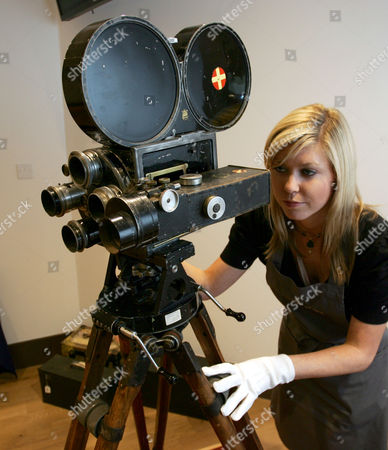 Stock Image of Samantha Ryan Christie's saleroom assistant Samantha Ryan poses with a Bell and Howell model 2709 motion picture camera, the personal movie camera of Charlie Chaplin and used to make several of his classic films, London, . The camera will be auctioned Wednesday and is estimated to sell for 70,000-90,000 British pounds (US$140,000-180,000