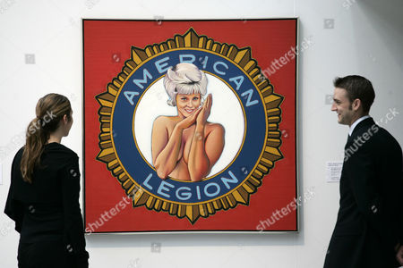 Two staff checks on a Mel Ramos' painting 'Miss American Legion' on display at Christie's in London,. The painting is to be auctioned in an 'Post-war and Contemporary Art Sale' on June 20 with an estimated price of 500,000 to 800,000 pounds (US$986,575 to 1,578,520 or 742,008 to 1,187,214 euro