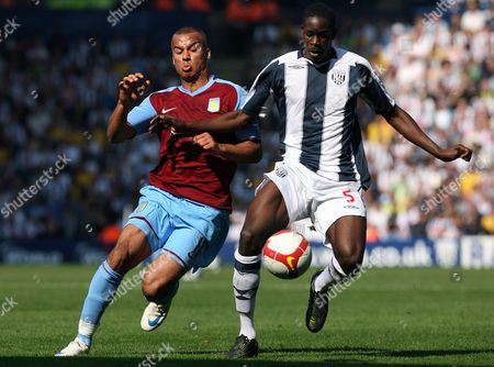 Aston Villa's Gabby Agbonlahor, left, battles for the ball with West Bromwich Albion's Leon Barnett during their English Premier League soccer match at the Hawthorns, West Bromwich, England