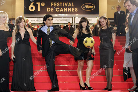 "Diego Maradona, Emir Kusturica, Dalma Maradona, Giannina Maradona Former Argentine soccer player Diego Maradona, center, juggles with a ball as he arrives, from left, with his former wife Claudia, his daughters Dalma and Giannina, and director Emir Kusturica for the premiere of ""Maradona"" during the 61st International film festival in Cannes, southern France, on"