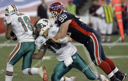 Stock Picture of Chad Pennington Miami Dolphins' Chad Pennington (10) hands off to Ted Ginn Jr., (19) under pressure from Buffalo Bills' Kyle Williams (95) during the first half of the football game at the Rogers Centre in Toronto