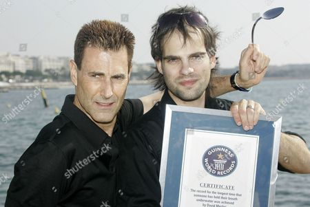 "David Merlini, Uri Geller Israeli-British illusionist Uri Geller, left, and Hungarian escape artist David Merlini pose with his ""Guinness World Record"" certificate during the 24th MIPCOM (International Film and Programme Market for Tv, Video,Cable and Satellitte) in Cannes, southeastern France, . Merlini seted up a new underwater-world record in 20 minutes and 39 seconds while being lowered in a tank of water, breaking the previous record of 17 minutes and 19 seconds"