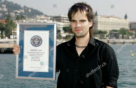 "David Merlini Hungarian escape artist David Merlini poses with his ""Guinness World Record"" certificat during the 24th MIPCOM (International Film and Programme Market for Tv, Video,Cable and Satellitte) in Cannes, southeastern France, . Merlini seted up a new underwater-world record in 20 minutes and 39 seconds while being lowered in a tank of water, breaking the previous record of 17 minutes and 19 seconds"