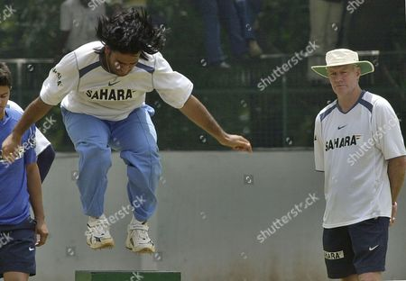 Mahendra Dhoni, Greg Chappell Indian cricketer Mahendra Dhoni jumps over an obstacle as team coach Greg Chappell, right, looks on during a training camp in Bangalore, India, . The Indian cricket team is preparing for the tri-nation series tournament in Malaysia featuring Australia, West Indies and India, commencing on Sept. 12