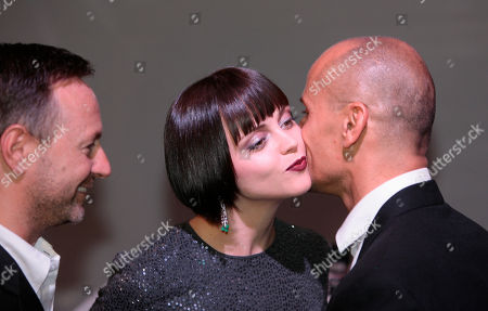 Christina Ricci, Mark Carrasquillo, Kevin Carrigan Actress Christina Ricci, center, receives a kiss by Mark Carrasquillo, the Global Make-up artist of ck Calvin Klein beauty, as Kevin Carrigan, the Creative Director of ck Calvin Klein looks, in Milan, Italy