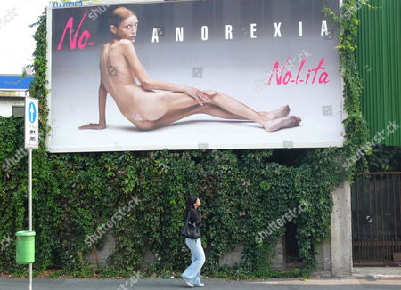A woman looks at a giant poster showing French model Isabelle Caro, part of a campaign against anorexia by Italian photographer Oliviero Toscani, in Milan, Italy. Caro's longtime acting instructor, Daniele Dubreuil-Prevot, told The Associated Press on that Caro died on Nov. 17 after returning to France from a job in Tokyo