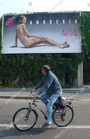 A man looks at a giant poster showing French model Isabelle Caro, part of a campaign against anorexia by Italian photographer Oliviero Toscani, in Milan, Italy. A French actress and model whose anorexic image appeared in a shock Italian ad campaign, Isabelle Caro, has died at age 28. Her longtime acting instructor, Daniele Dubreuil-Prevot, told The Associated Press on Wednesday that Caro died on Nov. 17 after returning to France from a job in Tokyo