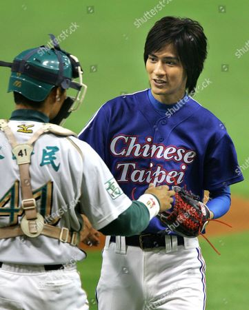 Vic Chou, Chen Feng-Min Taiwanese top singer Vic Chou gets a ball from Taiwan's La New Bears catcher Chen Feng-Min after throwing the ceremonial first pitch for the game between Taiwan's La New Bears and Japan's Nippon Ham Fighters in the Asia Series baseball tournament at Tokyo Dome in Tokyo