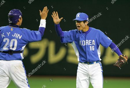 JIN KIM South Korea's reliever Kim Jong-kook (16) makes a high-five with catcher Jin Kab-yong after beating Taiwan 2-0 in their Asia Round game of the World Baseball Classic at Tokyo Dome in Tokyo