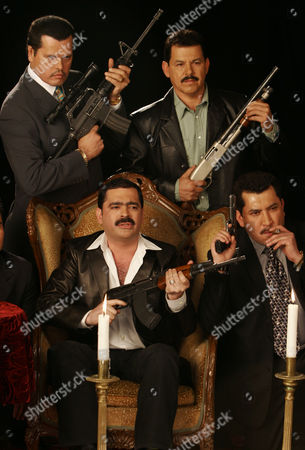 """Mario Quintero Lara, Mario Moreno Quintero, Clemente Flores, David Servin Members of the norteno band Los Tucanes de Tijuana, Mario Quintero Lara, seated center, Mario Moreno Quintero, top left, Clemente Flores, top right, and David Servin pose with guns during the filming of their music video for their song """"El Papa de los Pollitos"""" in Mexico City. Lead vocalist Mario Quintero said on Feb. 19, 2011 that the band hopes to return soon to the stage in Tijuana, after being banned from performing in the city in 2008 by then city police chief after the group publicly greeted two reputed drug lords during a concert"""
