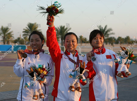 SHOOTNG South Korea's bronze medalist Kim Byung Hi, China's gold medalist Tao Luna, and China's silver mdalist Guo Wenjun celerate their victory in the Asian Games shooting women's 10m air pistol in Doha, Qatar